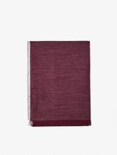 Foulard uni à contour contrastant, confectionné en modal et laine. Finition effilochée sur les bords.