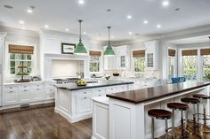 A dual island kitchen featuring white marble and stained wood countertops. Green…