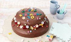 Kinder-Geburtstagstorte Rezepte: Doppelstöckige Torte aus Zebrakuchen, Zitronenkuchen und Schokoguss mit Blümchen und Schokoladen-Buchstaben für Kinder. | Dr. Oetker