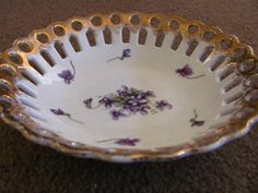 "Vintage reticulated or latticed fruit bowl with violets and gold trim on the scalloped edge.8"" in diameter. 2"" deepCirca 1950.Made in Japan.Very nice condition. No chips, cracks or crazing. Bright colors."