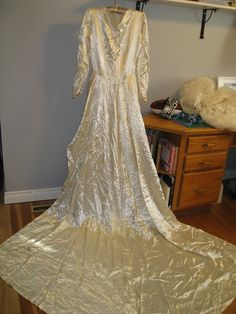 Early 1940's satin wedding gown.  Metal side zip and peplum front falling into long train.