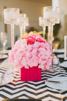 Black & white table with pink centerpiece's and elegant candles.