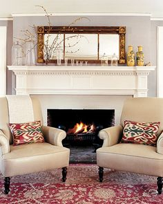 Living Room Detail    By the fireplace, two monochromatic armchairs are enclosed by a rich patterned rug and ikat pillows, which give the room a bohemian quality.  MarthaStewart.com