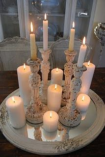 Old candlesticks mixed with regular candles on top of a vintage mirror