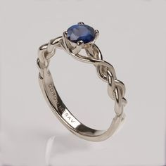A handmade 14K white gold braided ring set with a natural blue sapphire.  The ring in the pictures is set with a 5mm blue sapphire but can be set with
