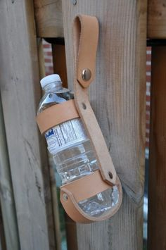The Bottle Harness holds a 500ml water bottle, and allows you to hook it onto your belt, or backpack, or wherever you choose. Made from heavy 8 oz. leather, 1 inch wide, riveted solidly together, and left undyed. A handy way to haul your bottle of water with you. Great for hikes, or biking, or... Snap it over, or slide it onto your belt. Will fit belts up to 2 inches wide. Has a solid nickel silver dome snap closure. This is a solid carrier that will last for ages! Bottle and w...