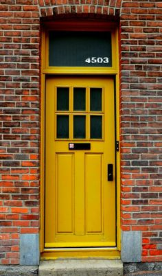 Montreal, Quebec, Canada. Mustard door with transom, step, windowed, plaqued, beveled.