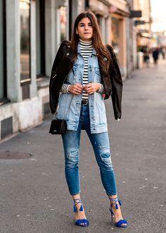 Mulher morena parada na calçada tira foto para street style vestindo turtleneck de listras, jaqueta jeans, jaqueta de couro, calça jeans destroyed, salto alto azul, bolsa a tiracolo preta