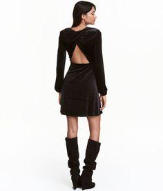 Schwarz. Kurzes Kleid aus weichem Velours mit feinem Glanz. Rückenteil im Wickelschnitt mit Cut-out. Lange Ärmel mit elastischem Abschluss. Teilungsnaht in