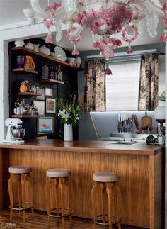 """Um balcão de freijó divide sala e cozinha, onde Rita testa suas receitas, publicadas no blog e em livros como o Cozinha de Estar (ed. Paralela). O cinza cobre paredes e armários (Marcenaria Baraúna). """"A integração trouxe muita luz, o que me permitiu usar esse tom"""", diz Rita."""