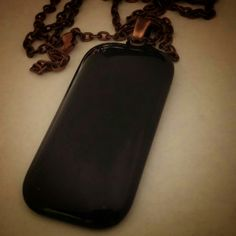 Black rectangular glass pendant with copper colored bail.