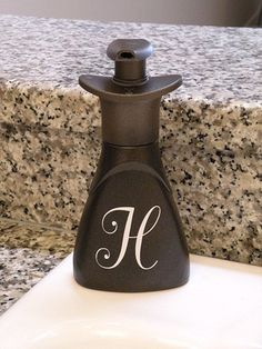 Originally a plastic Dawn hand-soap bottle. Bronze spray paint and a monogram sticker. Refill as needed. [fancy shmancy]