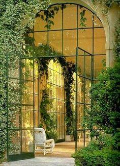 Galería exterior acristalada, arquitectura francesa, con altos arcos y vegetación.