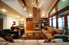 Open living room with dark and light colored furniture, a stone fireplace, eclectic chandelier and hardwood floors. They redid it all. Click on the pin to see if you can handle a remodel in your home! #livingroom