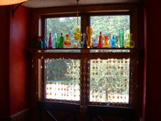 Colored glass on window shelf with unique window treatment.