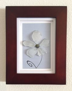 Genuine sea glass collected from a beach on the central coast of California arranged into a flower with a baby blue background. 9 x 7 glass