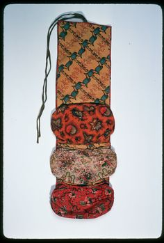 c. 1830.  19th century sewing kit.  Cylinder-printed cotton housewife with three bag-like pockets. Pockets are rounded at the bottom and gathered to piping at top and bottom. An olive woven tape with then red stripe is attached at the top edge to tie the housewife when it is rolled up for storage. Backing fabric is pulled to the inside as binding.