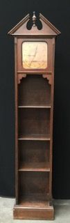 1920S-1930S BOOKCASE CLOCK STYLED TO GIVE IT A GRANDFATHER CLOCK LIKE APPEARANCE. THE BRASS FACE PLATE READS ELECTRIC AND IT HAS 4 SHELVES FOR BOOKS OR KNICK KNACKS. MEASURES 68 INCHES HIGH BY 16 INCHES ACROSS AND 10 INCHES DEEP.