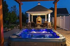 bullfrog hot tub with a view night shots, outdoor living, pool designs, spas, Bullfrog Spa custom design and installation by Long Island Hot Tub Melville New York next to a gas fireplace and Pavilion night photo