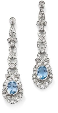 A pair of aquamarine and diamond ear pendants.  Each designed as an oval-shaped mixed-cut aquamarine within a palmette old brilliant-cut diamond cluster to an articulated entwined single-cut diamond line surmount, length 5.5 cm, French import marks.