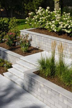 This retaining wall idea is inspired by our G-Force wall block. The smooth texture produces a modern look and is available in two grey tones and two brown tones to provide greater design versatility. Backyard Retaining Walls, Retaining Wall Design, Sloped Backyard, Backyard Patio Designs, Front Yard Landscaping, Rock Retaining Wall, Landscaping Ideas, Retaining Wall Gardens, Retaining Wall With Steps