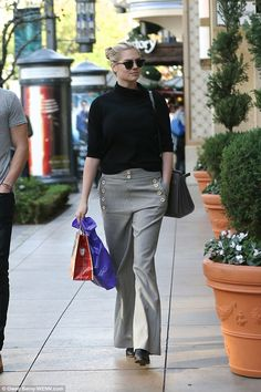 Black and white: The stunner rocked her off-duty style in wide-legged checked trousers and...