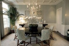 Pale blue/grey walls, bright white wainscotting, an arrangement of framed coral, coffered ceilings, a large dark wood round table, beautiful dining chairs upholstered in a light blue fabric, a gleaming metal chandelier make for a serenely luxurious dining room