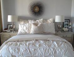 Lovely city bedroom design with sunburst mirror, Hollywood Regency cabinet nightstand, gray, blanket, silver urn lamps and West Elm pin-tuck duvet & shams.