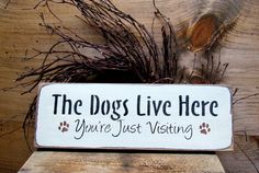 """This wooden sign is made from pine, and measures Approx 4.5""""W x 13""""L. It reads """"The Dogs Live Here ... You're Just Visiting"""". The front is painted Craft White then distressed, the back is stained with"""