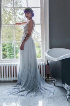 Heart of Glass is our favourite new wedding dress design. Heart of glass is an ivory tulle dress dip dyed in a subtle and beautiful frost grey colour. This dress has 800 tiny flowers hand sewn all over the top. This dress takes hours and hours of hard work making sure the flowers are positioned and sewn in place...But it is worth it! If you want that wow factor then Heart of Glass is the one for you. She has a large train and a low V neck back. This dress is available in any colour.She's...