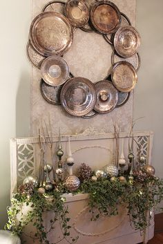 I love the wall decorated with a giant wreath of silverplate trays and a wonderful old headboard and footboard turned into a planter...