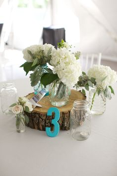 Wood and Mason Jar Centerpiece - I like the tree slice under the flowers! Don't know if that's too rustic for our fancy place settings though