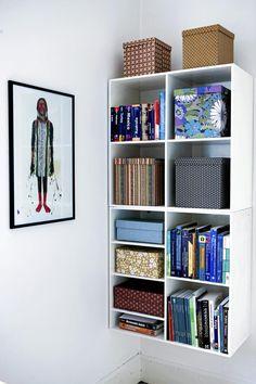 Hyllen er hengt opp i hjørnet av veggen, og fylt med esker og bøker i ulike farger og mønstre. Dette er en fin måte å live opp et fargeløst interiør på.