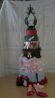 A Wizard of Oz Themed  cake made of round boxes, fabrics and a variety of trims.