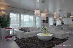 Celý dům je zařízen nábytkem v moderním duchu. Strohé linie jsou zútulněny doplňky, například skleněným lustrem nad sedací soupravou.