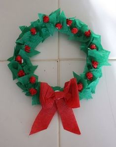 Torn green crepe paper, crumples red crepe paper berries,glued to paper plate with the middle cut out