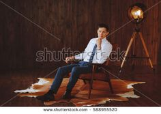 Portrait of business man in white shirt and blue tie. The loft style. Background dark wood. Retro lamp