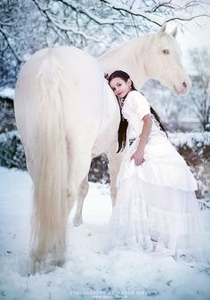 Girl in White with White Horse in Snow