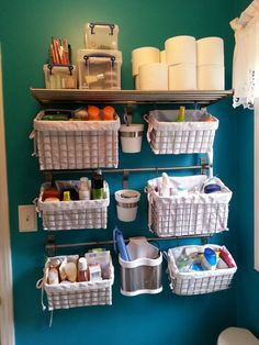 "My version of the ""small bathroom storage"" idea. Shelves, rods,  hanging pots from IKEA, baskets from CB2. LOVE how this keeps what I need close @ hand, but looks neat  pulled together in VERY SMALL master bathroom toilet/shower area."
