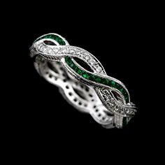 Eternity design band is made of 18K white gold and contains round cut diamonds (.36Cttw, G-VS quality) pave set and green emeralds (.35Cttw) channel set. Wedding ring is engraved on the sides and top