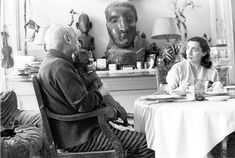 Jacqueline and Pablo Picasso seated at the dining table; Lump, in Picasso's lap, tries to lick the artist's face.