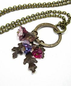 A lovely Boho Chic necklace featuring a 25mm Vintaj brass eternity garden ring holding loads of pretty little Czech glass flowers in shades of fuchsia, violet, and purple over a 31.5 x 26mm Vintaj oak frond. The antique brass chain is slightly over 19 inches long (48.3 mm) and closes with a floral toggle clasp.  The Vintaj Natural Brass Co. handmade process is eco-friendly Their products are not plated and are lead-free and nickel-free compliant. Each Vintaj brass embellishment undergoes a…