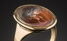 An antique hardstone and gold intaglio ring depicting the devil carrying cupid on his back