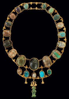 ufansius:  22 stone and faience scarabs (circa 2000 BCE-30 BCE) mounted with a Horus falcon amulet in a late 19th-century Egyptian Revival necklace.