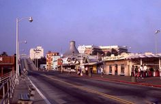 https://flic.kr/p/FjPKR8 | Looking east on the Santa Monica Pier, ca.1973 | Canopy-roof for the carousel center, and the arched sign for Sport Fishing and the end of the I-10 at the crest of the hill.