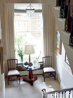 A double-height window floods the second-floor stair landing with sunlight.