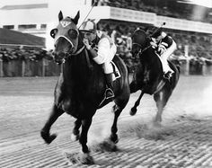 Seabiscuit and jockey George Woolf lead War Admiral and jockey Charles Kurtsinger in the first turn at Pimlico in Baltimore, Md., in this Nov. 1, 1938, photo. (Associated Press)