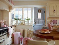 Cream sunlit country kitchen with pastel accessories and a stable door! Perfect, this is how I'm imagining our kitchen! Though I quite fancy part stainless steel worktops, and we've seen a nice pastel green stable door!