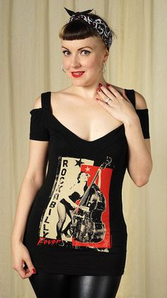 "This is a nice new take on a plain old T shirt! It's a black off the shoulder T with straps and the front features a Rockabilly pinup playin' the bass in red and tan and the words ""Rockabilly Fever"" down the left side. This image is by Viva Van Story"