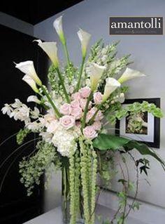 Arreglo en colores blancos, con azucenas, rosas, hortensias, amaranto en base de cristal para decorar la entrada de una oficina. www.amantolli.mx